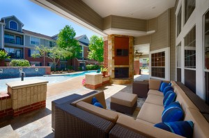 Two Bedroom Apartments for Rent in Katy, TX - Covered Outdoor Seating Area with Fireplace & TV and View of Pool